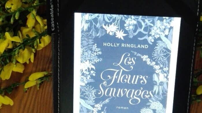 Liseuse avec la couverture du livre d'Holly Ringland, Les fleurs Sauvages. Genêts en arrière plan