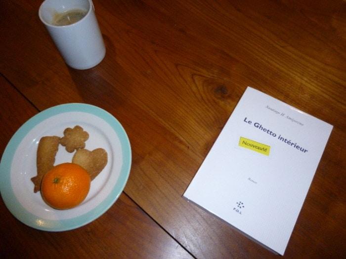Photo du livre de Santiago Amigorena, Le Ghetto intérieur sur une table avec un café et une assiette de gâteaux.