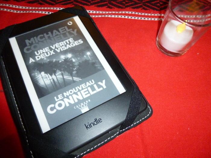 Liseuse avec la couverture du livre de Micahel Connelly, Une vérité à deux visages. Liseuse posée sur une nappe à côté d'un luminion.