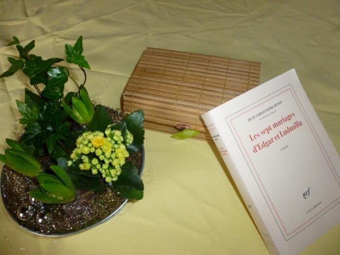 Photo du livre de Jean-Christophe Rufin Les sept mariages d'Edgar et Ludmilla sur une table avec un coffret et des hyacinthes.