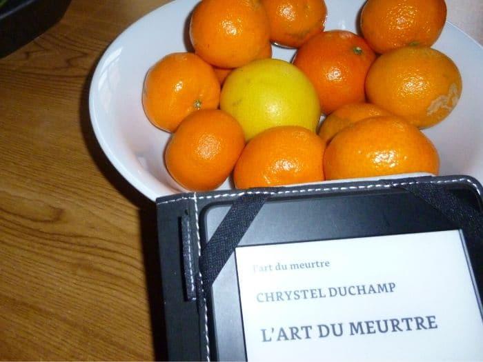 Liseuse posée sur une coupe de mandarine. Titre du livre de Chrystel Duchamp, L'art du meurtre