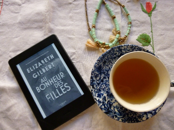 Tasse de thé, collier vert avec une liseuse ouverte sur le livre de Elizabeth Gilbert, Au bonheur des filles.
