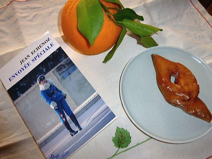 """Livre de poche """"Envoyée spéciale"""" de Jean Echenoz à côté d'une bugne et d'une orange"""