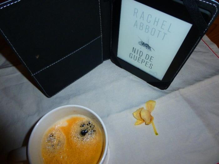Tasse de café, liseuse avec en couverture le livre de Rachel Abbott, Nid de guêpes