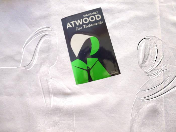 Livre de Margaret Atwood, Les testaments, entre deux statues en filigrane