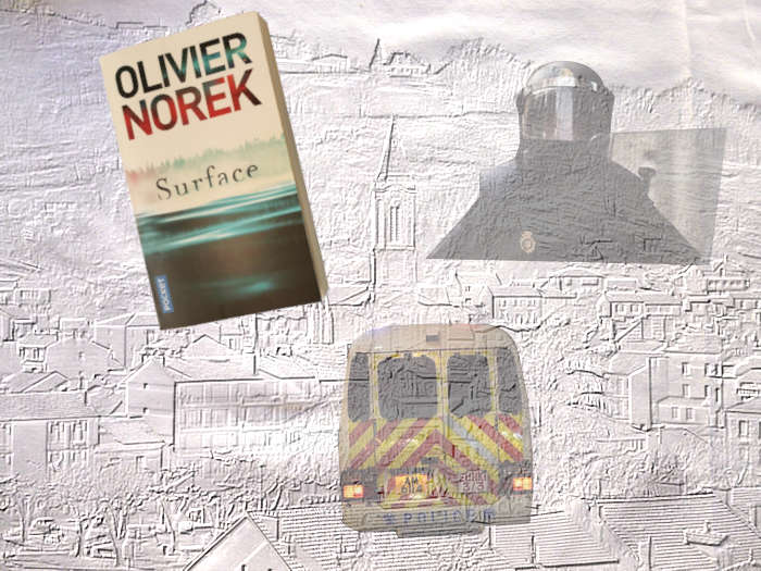 le livre d'Olivier Norek, Surface avec en fond la ville de Decazeville. Un casque de policier, une ambulance.