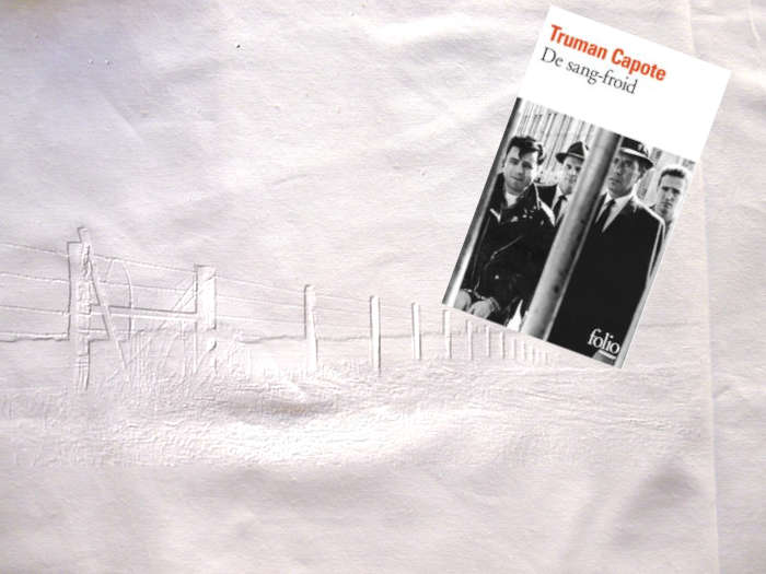Couverture du livre de Truman Capote, De sang-froid. En arrière plan une clôture qui court le long d'une prairie (Kansas)
