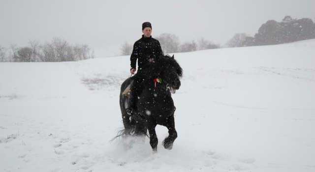 Homme à cheval dans un paysage de neige