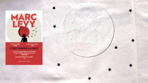 En arrière plan, la lune et des étoiles noires. Au premier plan la couverture du livre de Marc Lévy, C'est arrivé la nuit.