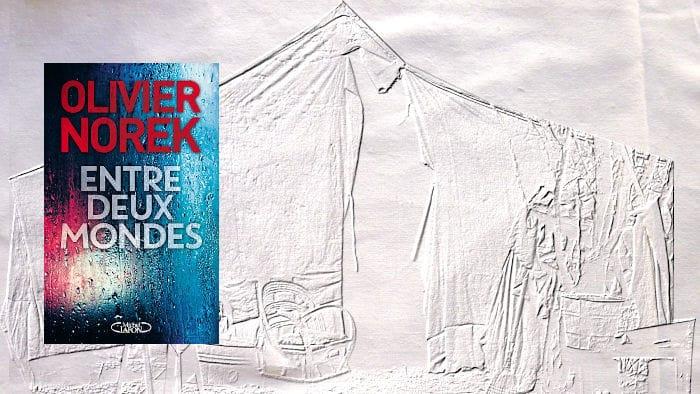 A l'arrière plan, une tente. Au premier plan, la couverture du livre d'Olivier Norek, Entre deux mondes