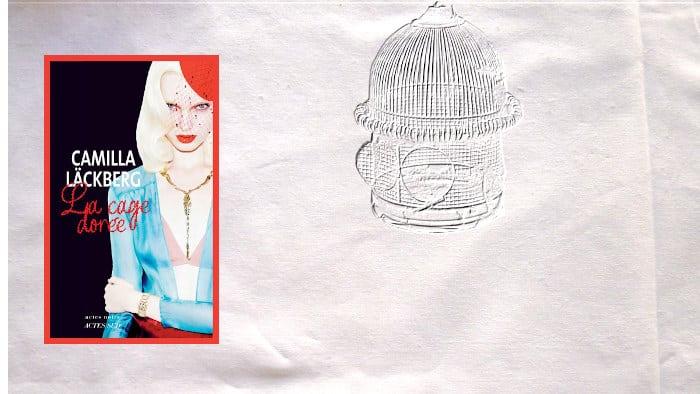 En arrière-plan, une cage ouverte, au premier plan, la couverture du livre de Camilla Läckberg, la cage dorée