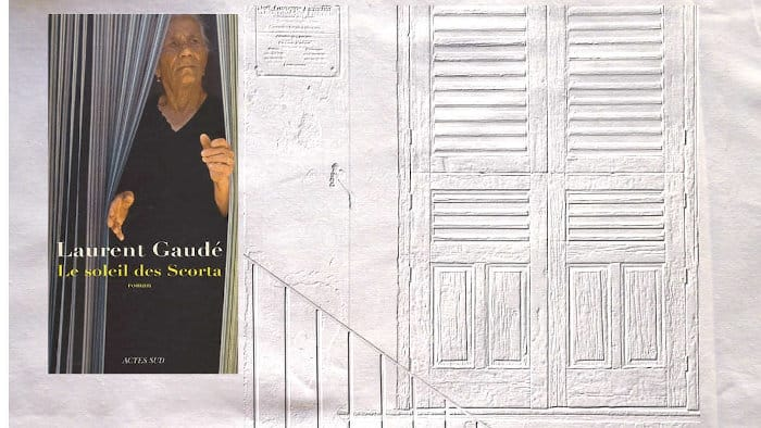 A l'arrière-plan, une fenêtre aux volets fermés, au premier plan, la couverture du livre de Laurent Gaudé, Le soleil des Scorta