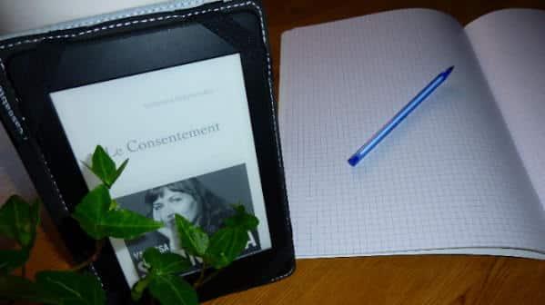 Liseuse avec la couverture du livre de Vanessa Springora, Le consentement. Cahier et stylo