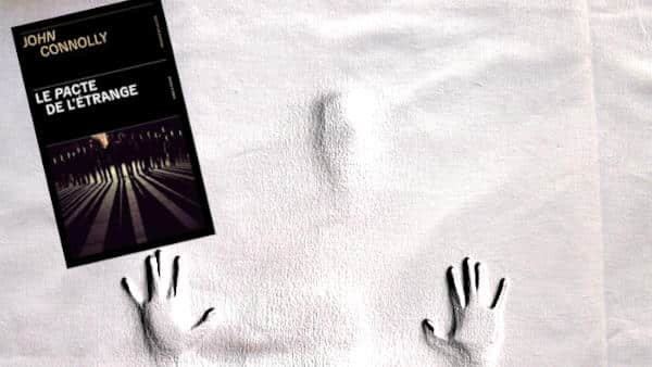 Couverture du livre de John Connolly, Le pacte de l'étrange avec en arrière plan l'esquisse d'un visage et de deux mains.