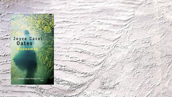 En arrière plan, de la boue, au premier plan, la couverture du livre de Joyce Carol Oates, Mudwoman