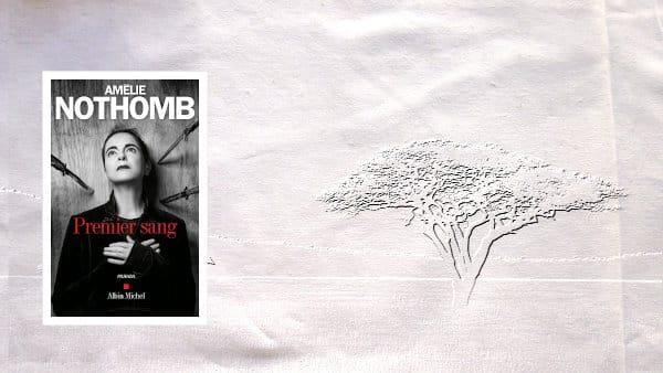 A l'arrière-plan, un arbre de la savane africaine, au premier plan, la couverture du livre d'Amélie Nothomb, Premier sang